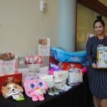 Woman stands beside table with baby supply donations